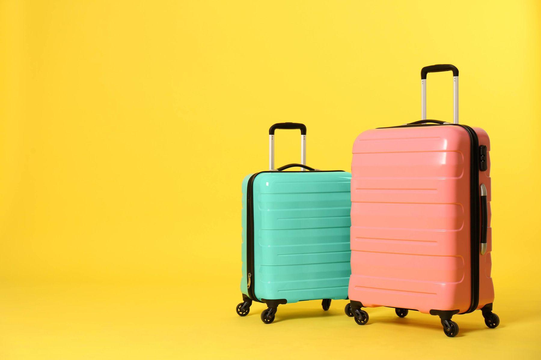 Mala grande de viagem cor de rosa ao lado de mala pequena verde sobre fundo amarelo
