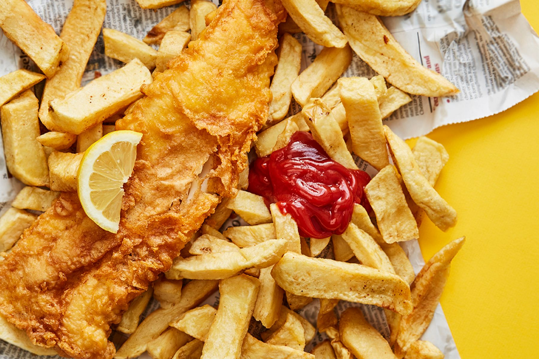 fish and chips on newspaper packaging against a yellow background