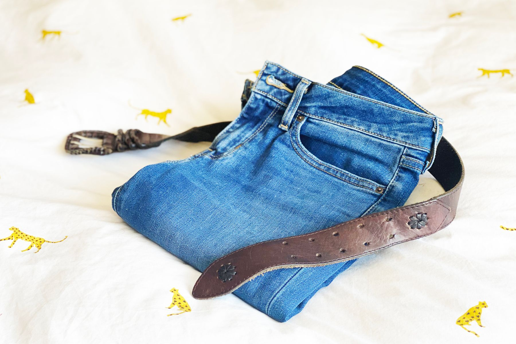 A pair of folded jeans and a belt on a bed