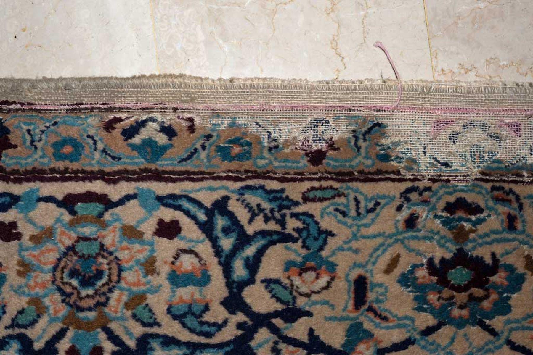 A moth eaten carpet on a stone floor