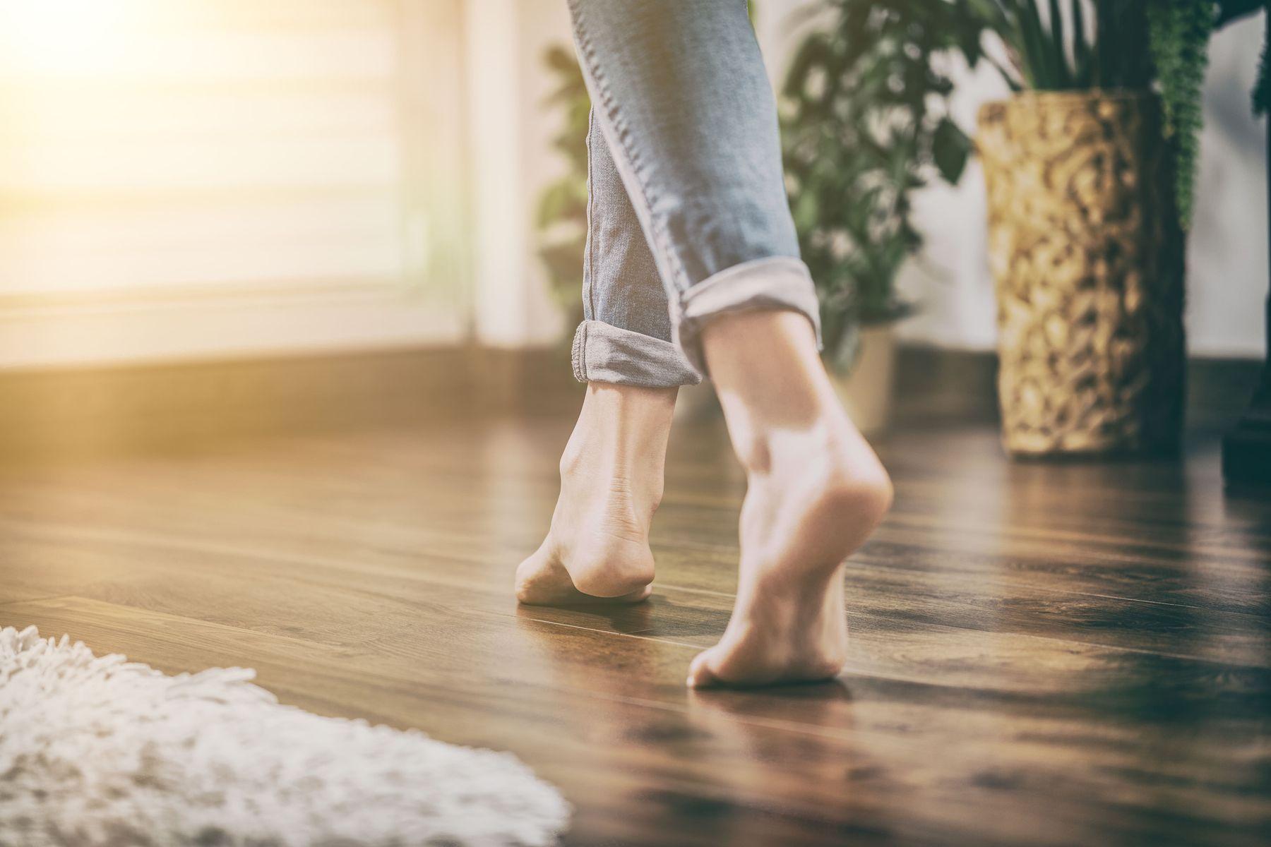 Mulher andando em piso brilhando, com vasos no chão e tapete