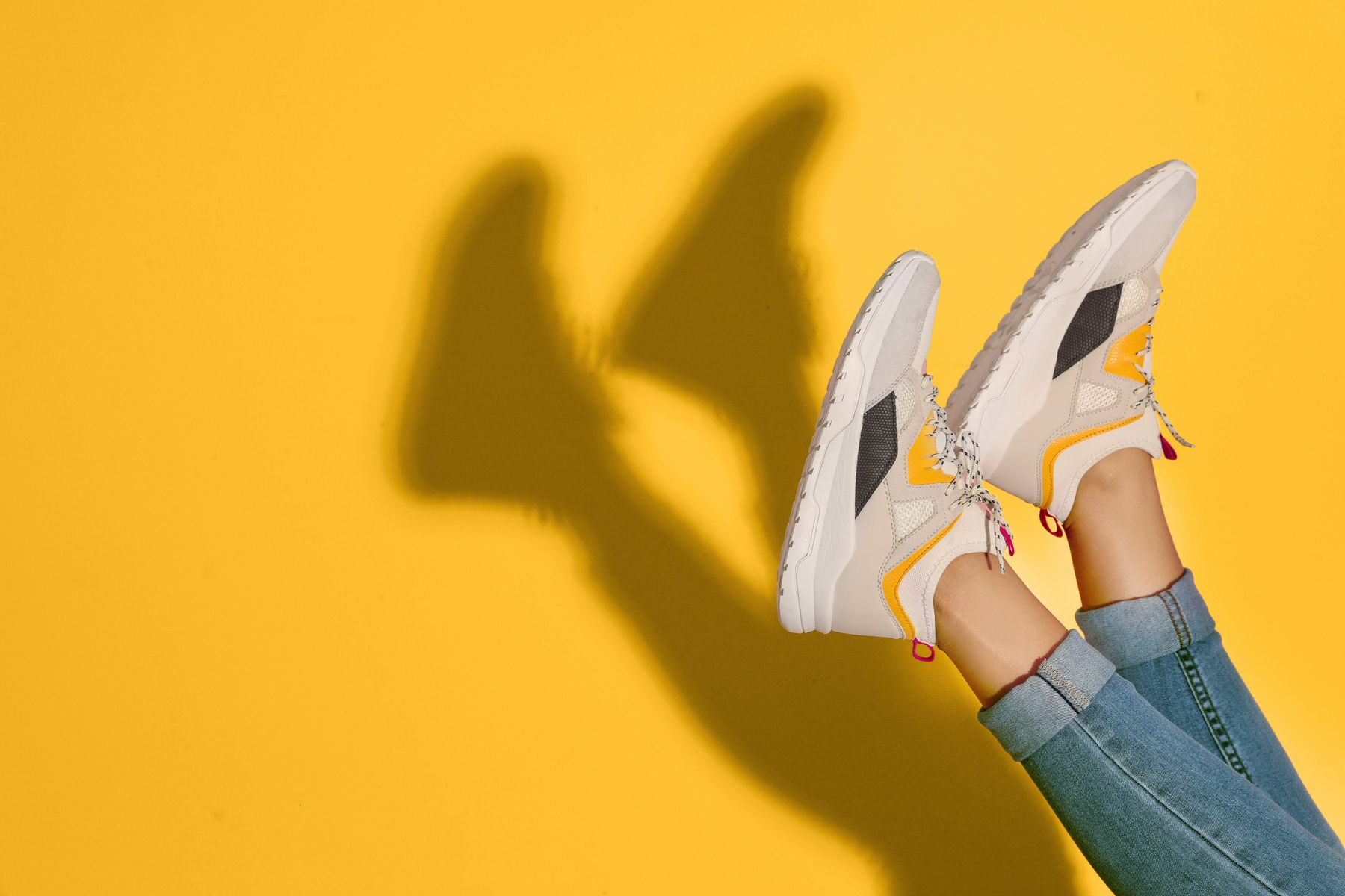 person wearing trainers on a yellow background