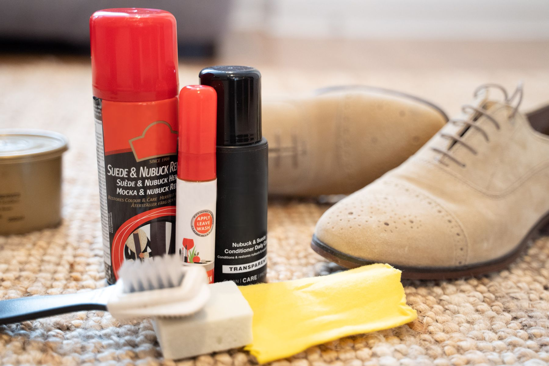 A collection of nubuck cleaning materials, including a nubuck brush, cloth and block