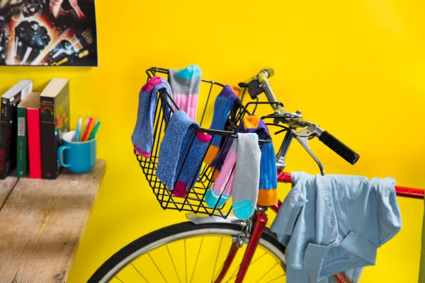 Bike basket containing socks and shelf with books as cleaning tips for busy millennials
