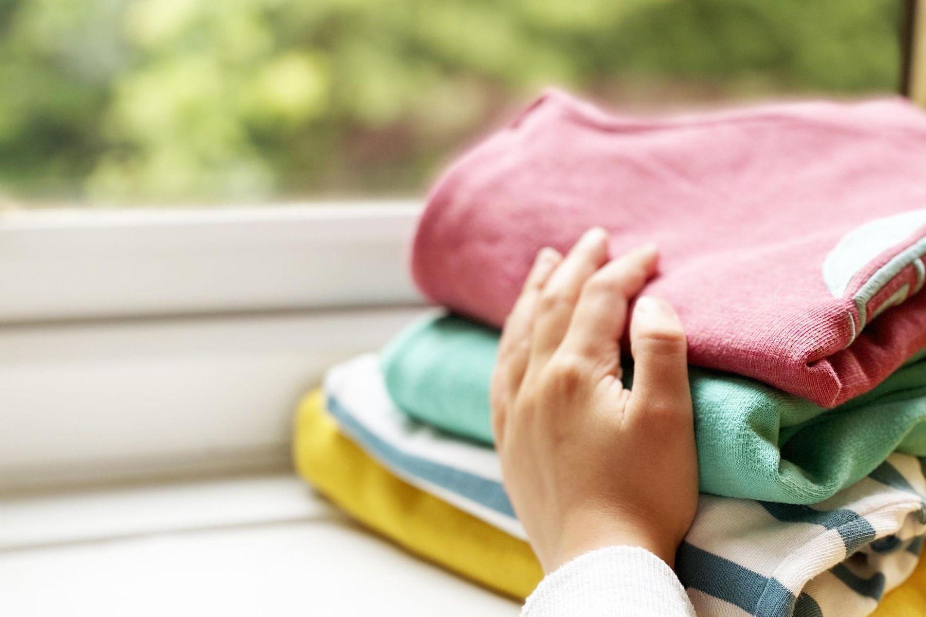 Mão feminina segurando pilha de roupas coloridas dobradas na janela