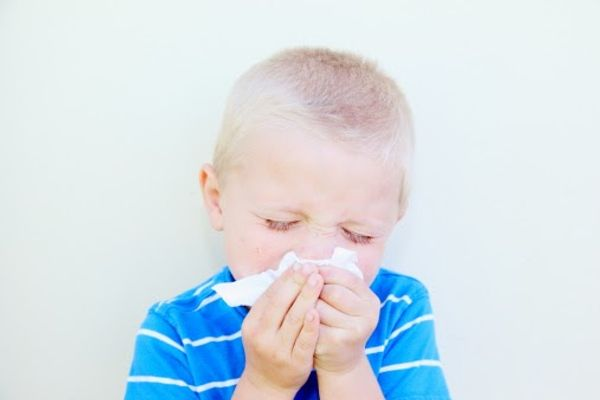 Boy blowing his nose with tissue paper