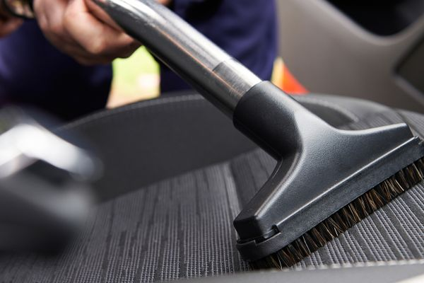 pessoa limpa banco do carro cinzento com escova de aspirador