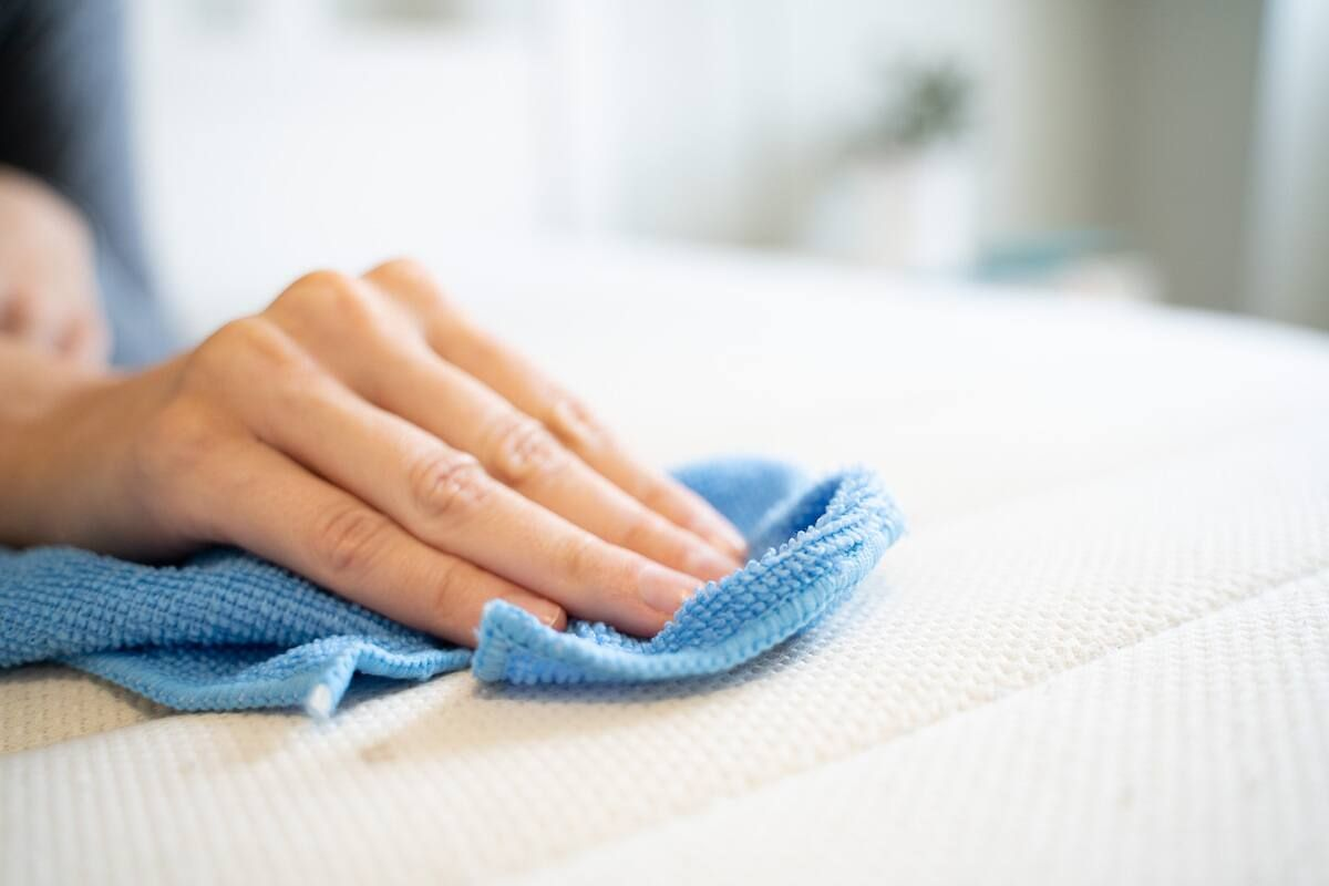 Hand cleaning mattress surface with microfibre cloth