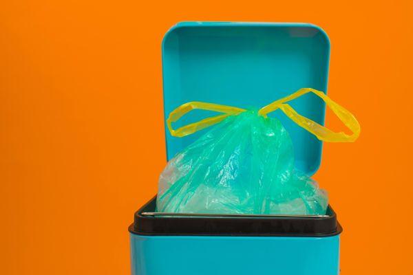 Lixeira azul com saco de lixo azul amarrado com uma fita amarela em um fundo laranja