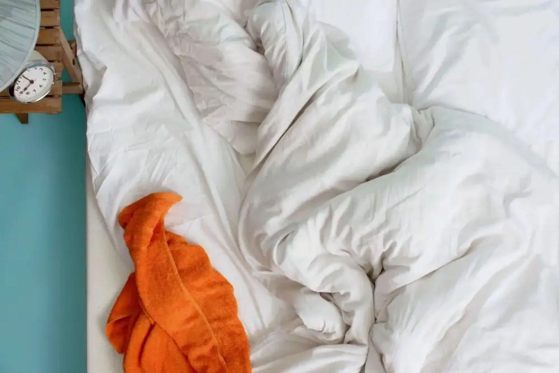 Step 3: Dağınık beyaz çarşaflar ve yorgan üzerinde turuncu havlu