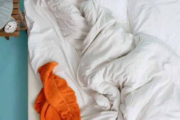 Dağınık beyaz çarşaflar ve yorgan üzerinde turuncu havlu