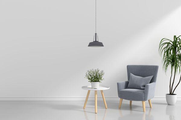 Sala com parede e piso branco com uma poltrona cinza, duas plantas e um lustre