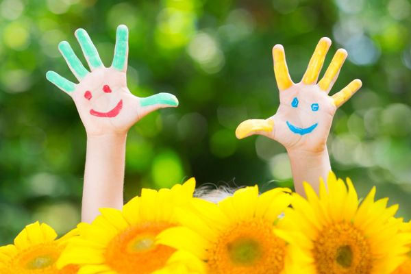 bemalte Kinderhände und gelbe Blumen im Garten