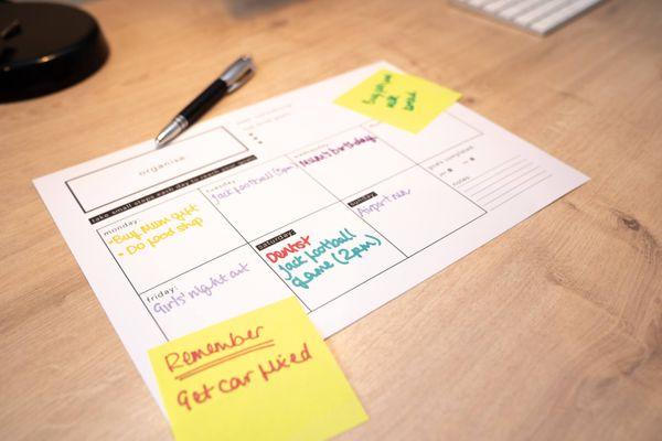Planer und Stift auf einem hölzernen Schreibtisch