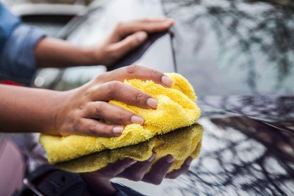 Pessoa limpando carro preto com flanela amarela