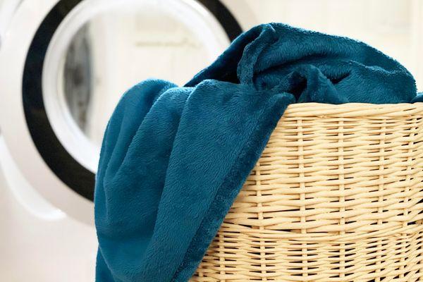 Mão coloca amaciante na máquina de lavar