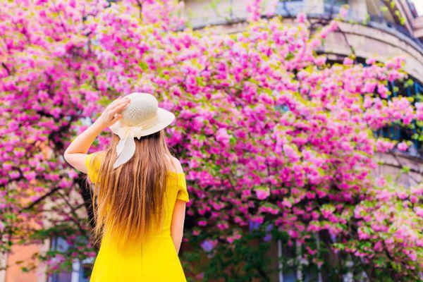 Junge Frau in gelbem Kleid vor bunt blühendem Baum