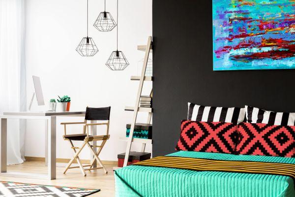 Quarto com dois ambientes, um com parede preta, com quadro azul pendurado e cama coberta com manta verde e almofadas coloridas e outro com uma parede branca com mesa, computador, estante e cadeira