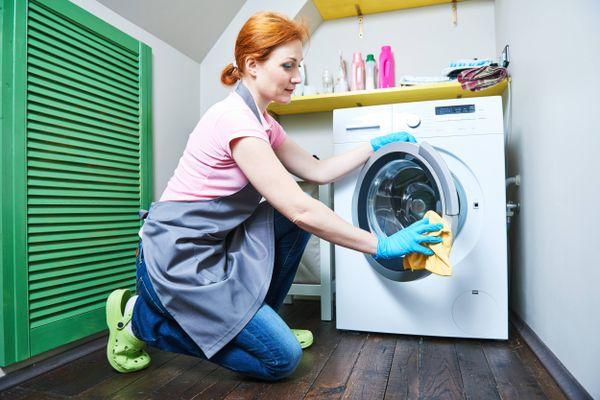 Mulher limpando a máquina de lavar com abertura frontal com pano