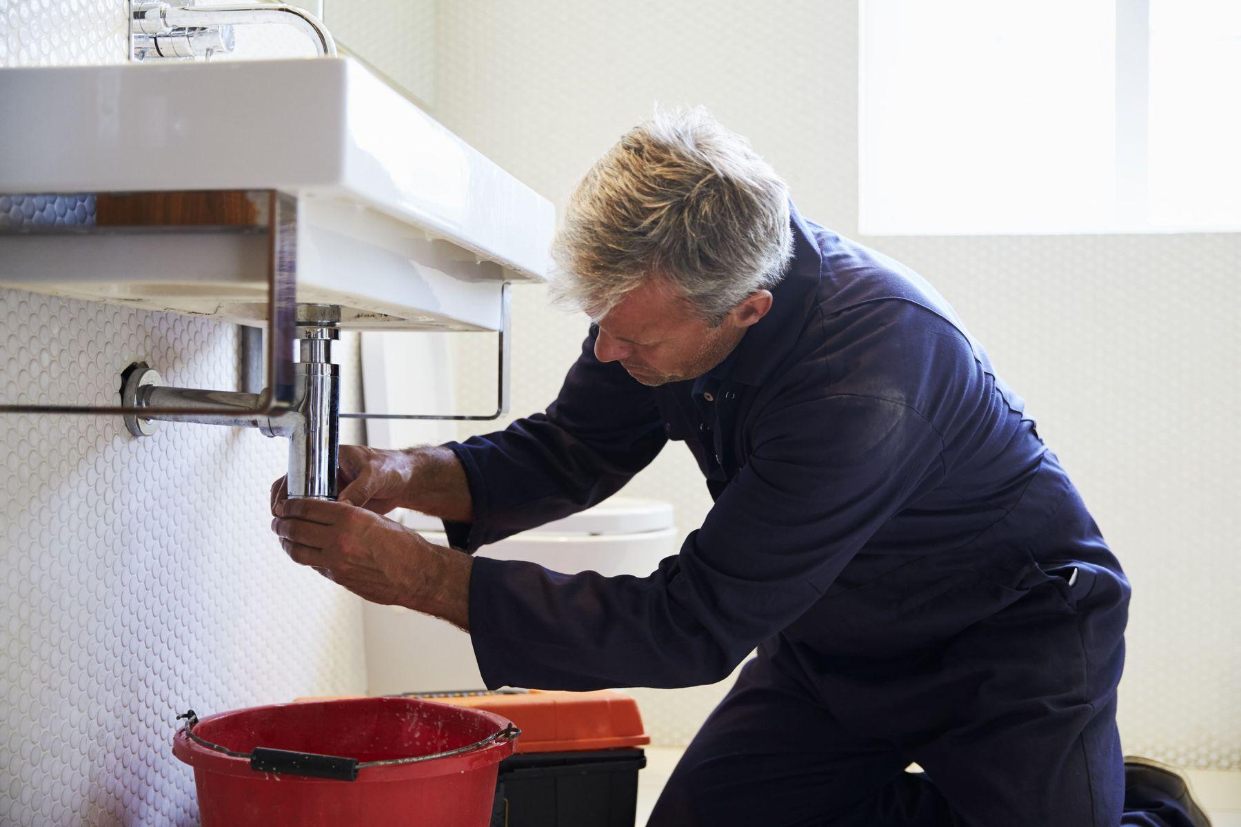 Homem arruma sifao da pia do banheiro
