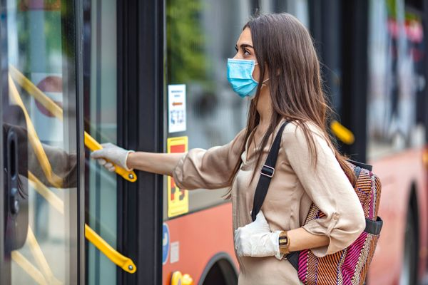 girl brown hair wearing mask boarding bus