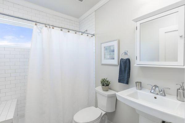 Bad mit Dusche, Waschbecken und Spiegel
