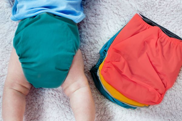 Baby wearing reusable cloth nappy next to washed cloth nappies