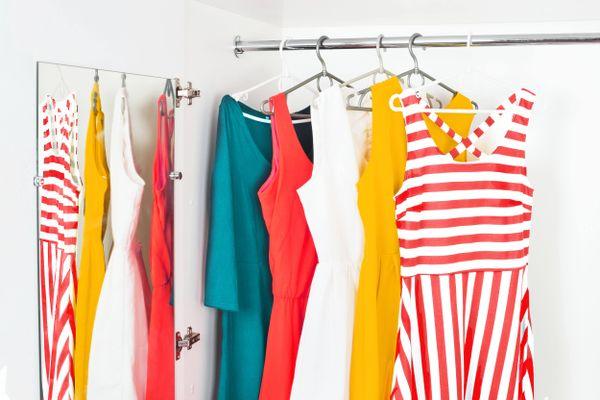 Armário branco aberto com vestidos coloridos pendurados