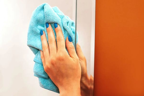A hand is holding a blue cloth wiping down the right edge of a mirror hanging on an orange wall