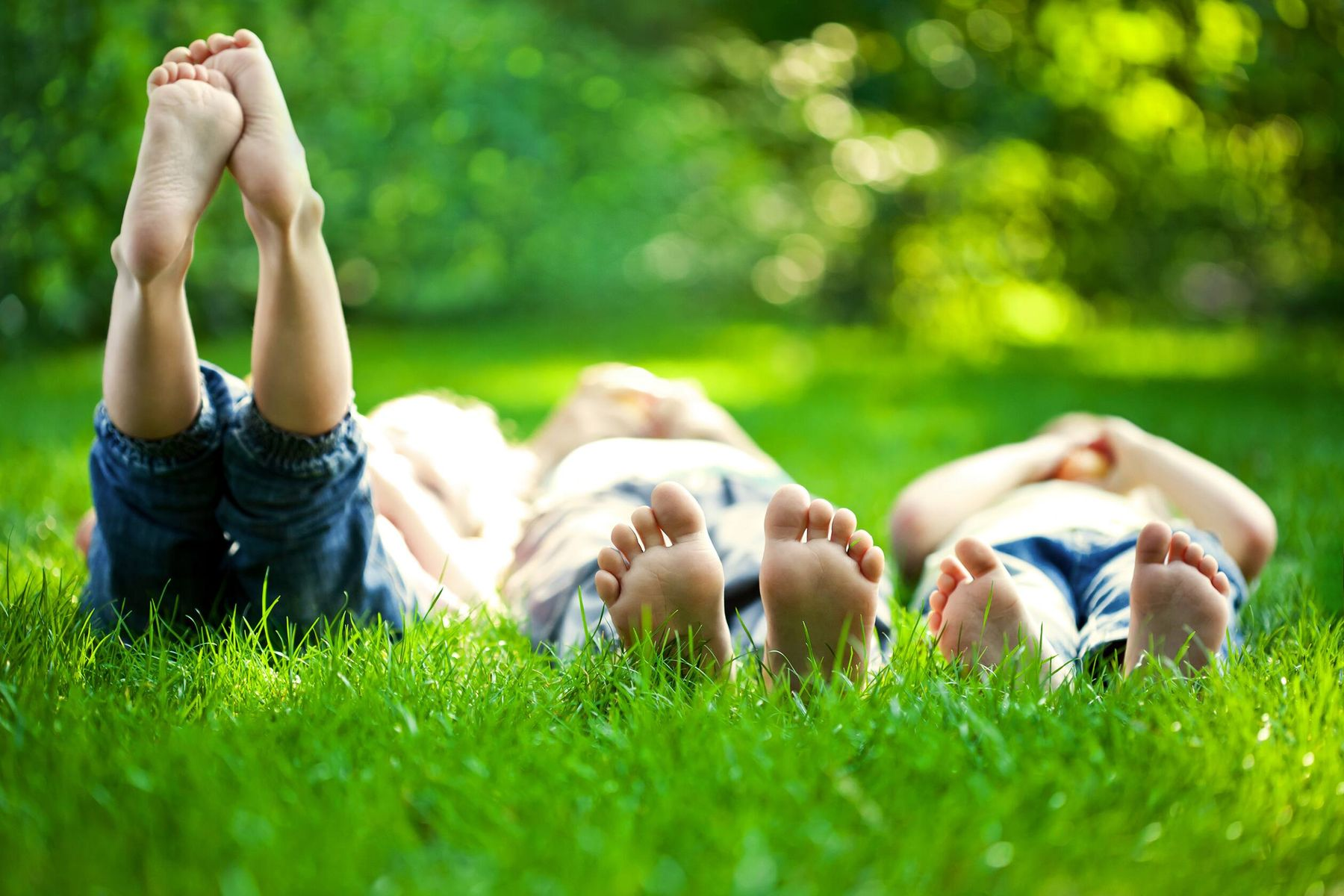 kids lay on grass outside in garden