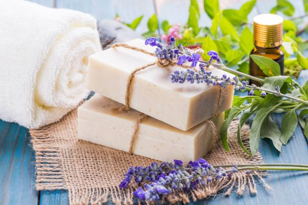 two bars of beige soap with lavender plants and a white towel