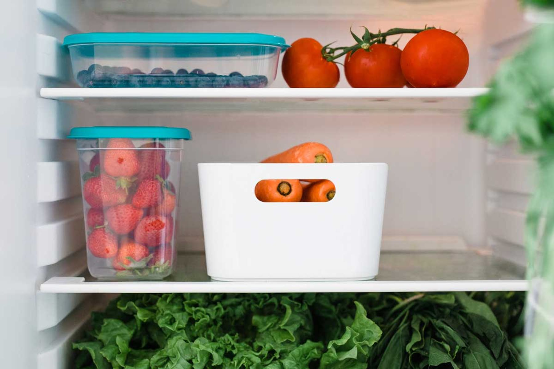 A view of the inside of a fridge with fruit and vegetables inside