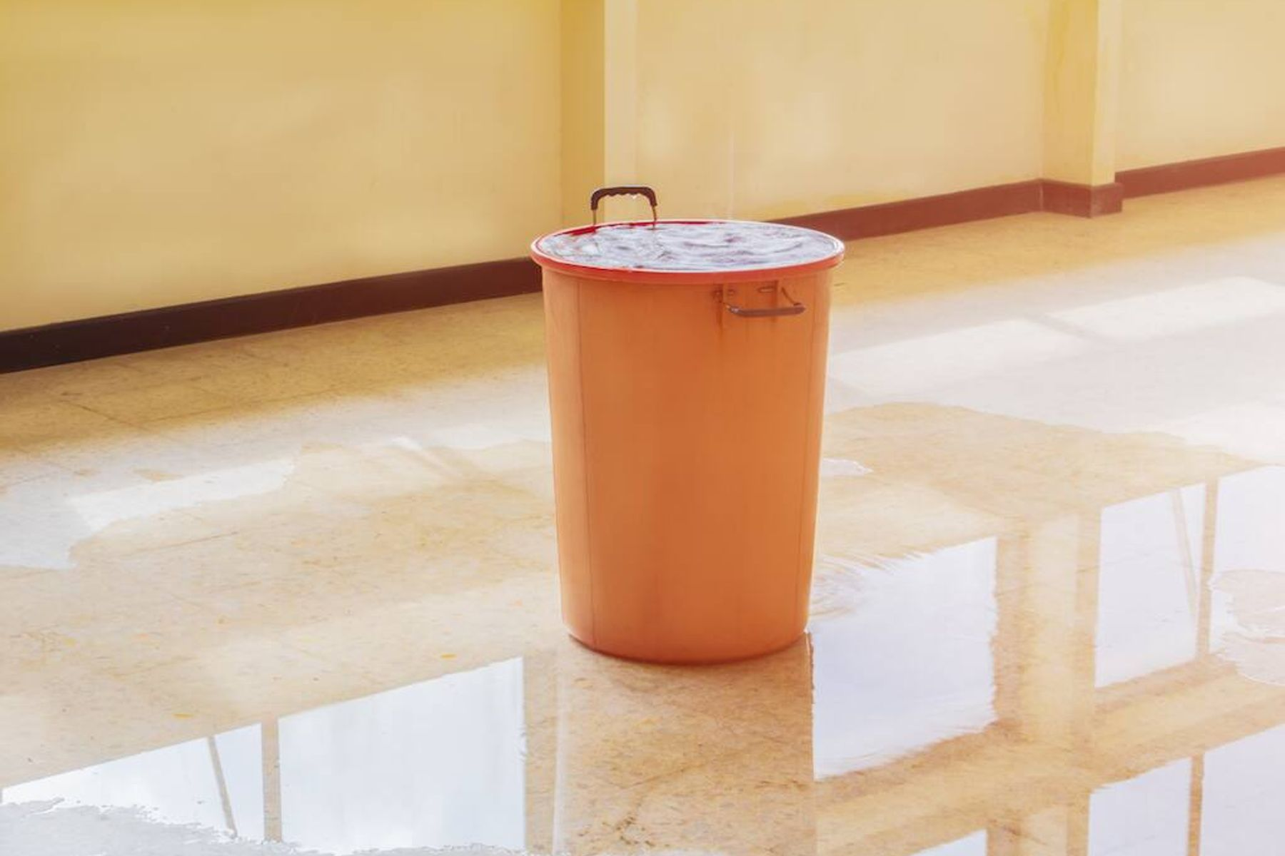An orange bucket in the middle of the floor, collecting water dripping from the ceiling