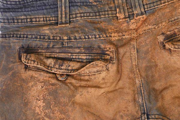 Calça jeans com manchas de barro