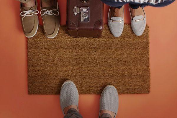 Blick von oben auf drei Paar Füsse mit Schuhen und eine Türmatte