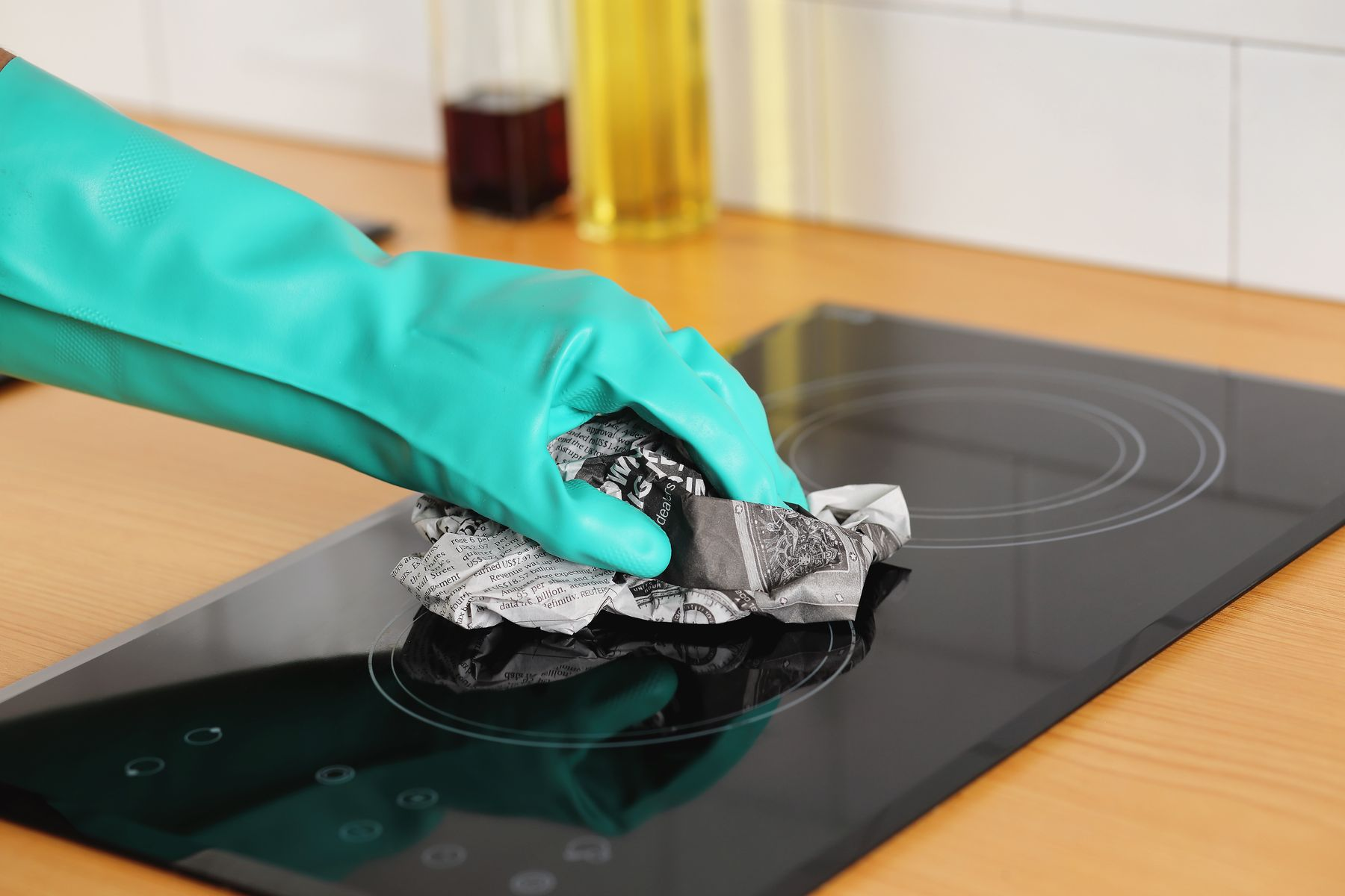 Step 4: Person using newspaper to clean hob