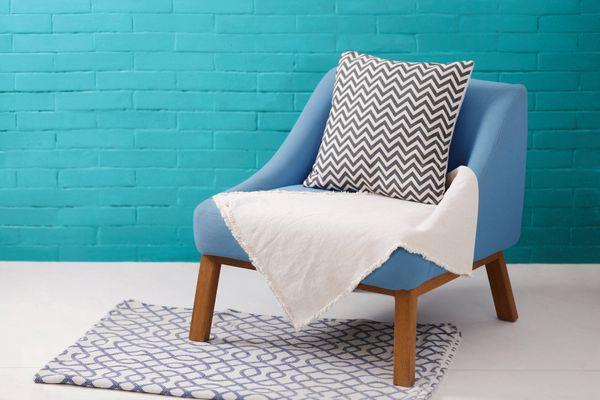 pared de ladrillos color turquesa con sillón y almohadon