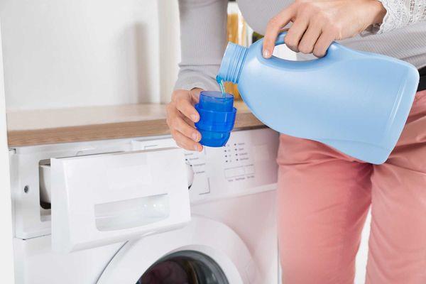 Đo liều lượng nước xả vải cho vào máy giặt