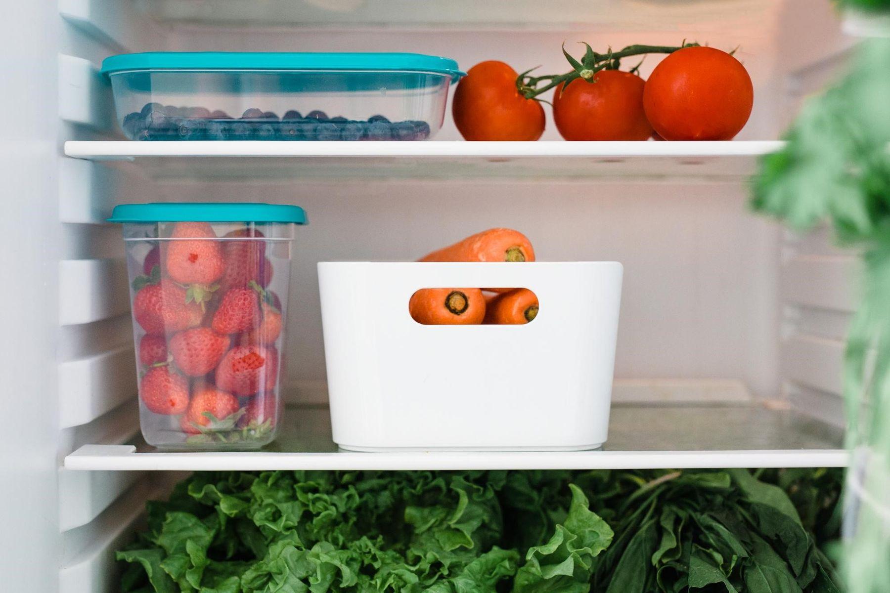 Prateleiras internas da geladeira contendo tomates, potes de mirtilo e morangos, vasilha com cenouras e prateleira com vegetais
