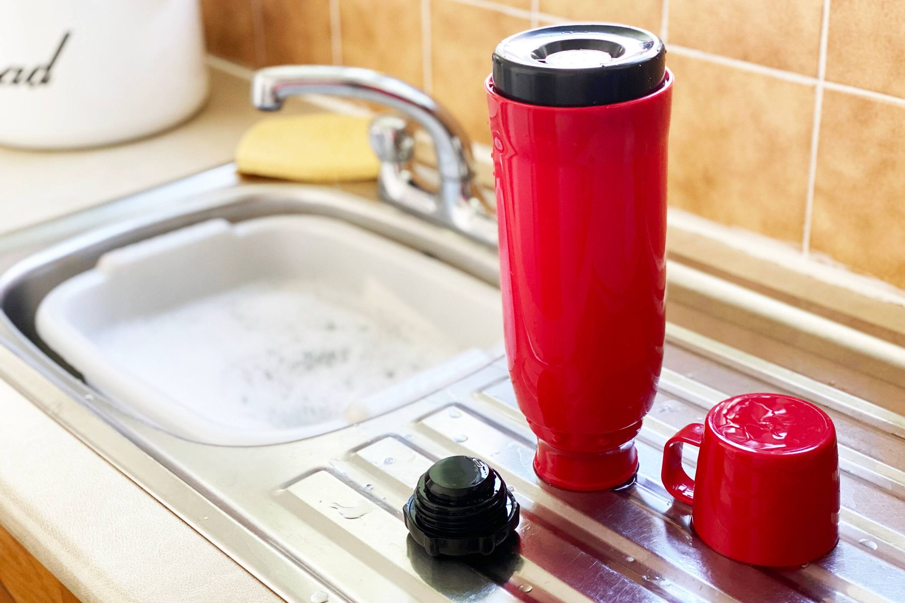 A flask, stopper and cup drying beside a sink