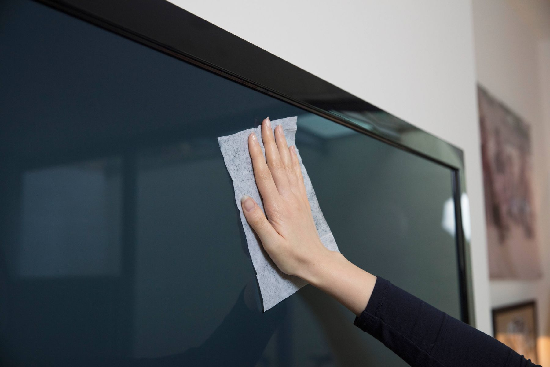 Pessoa passando um pano branco em cima de uma tela de tv