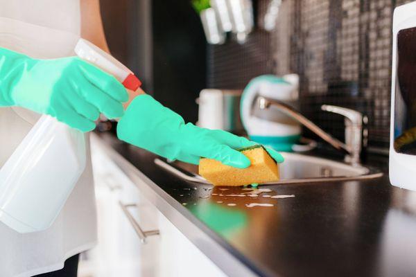 Pessoa limpando a bancada da cozinha com esponja e alvejante