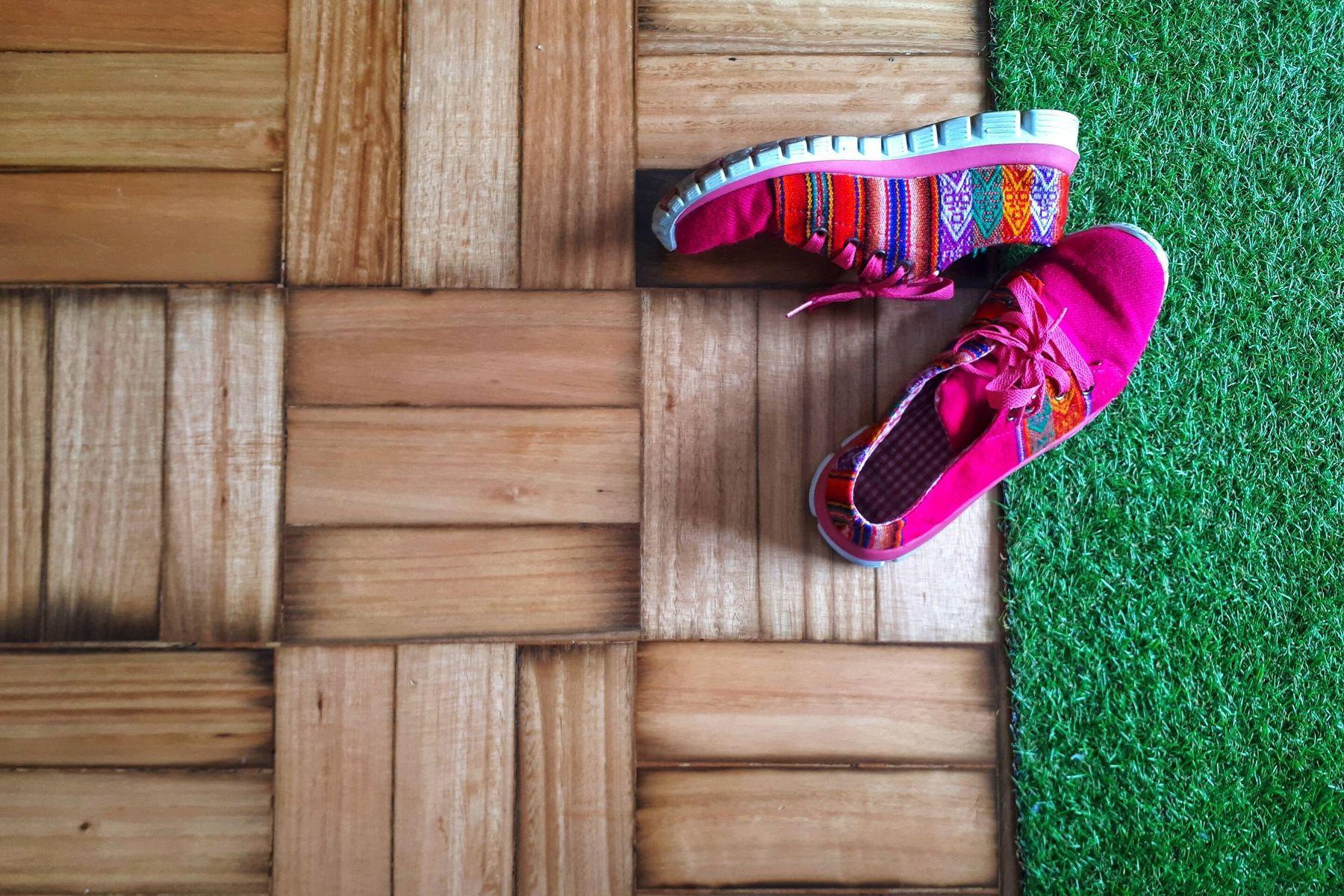 scarpe rosa sul pavimento di legno ed erba sintetica