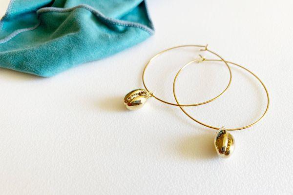 goldfarbene Ohrringe neben einem Mikrofasertuch