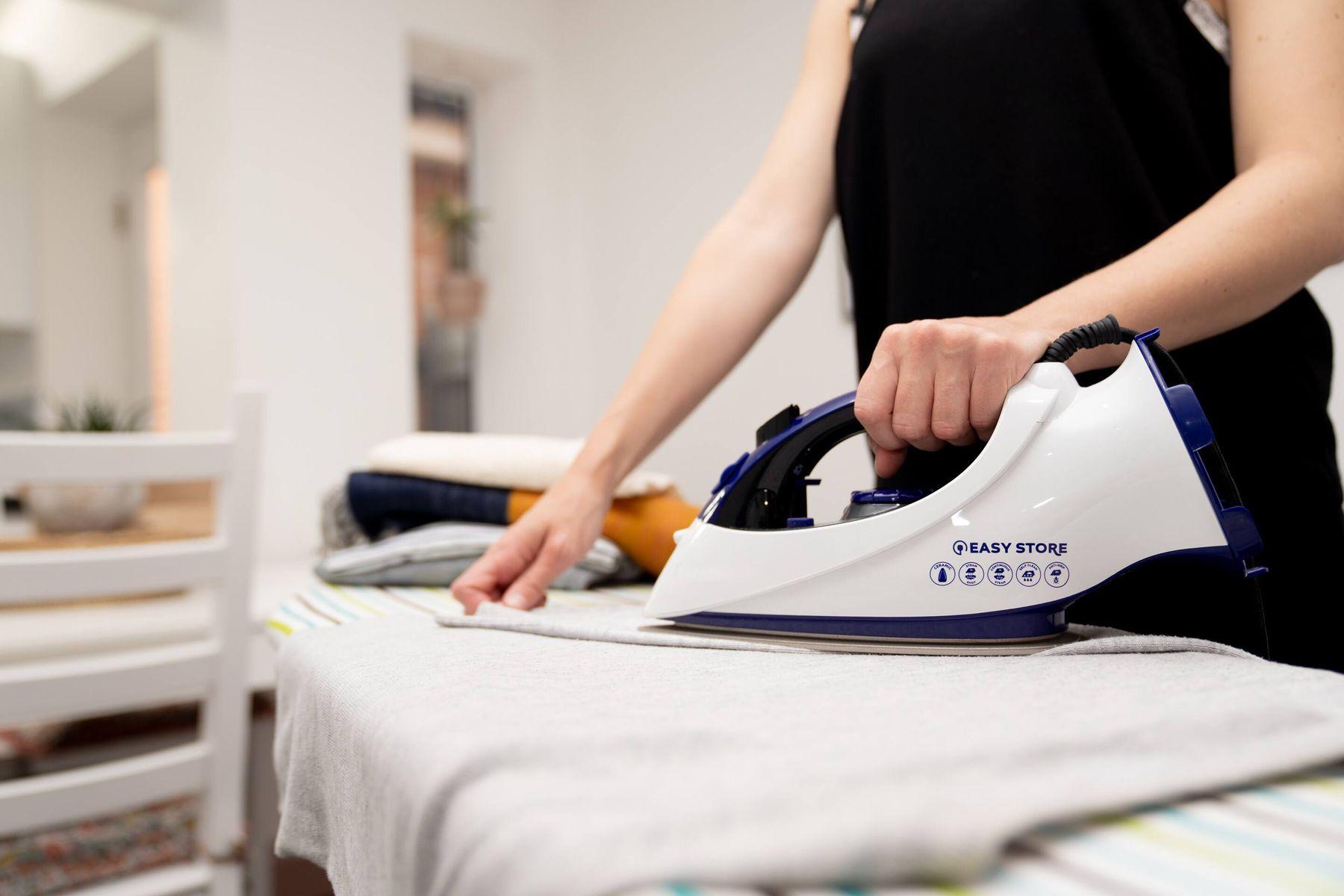 Ferro de passar roupa em primeiro plano passando uma roupa em uma tábua de passar.