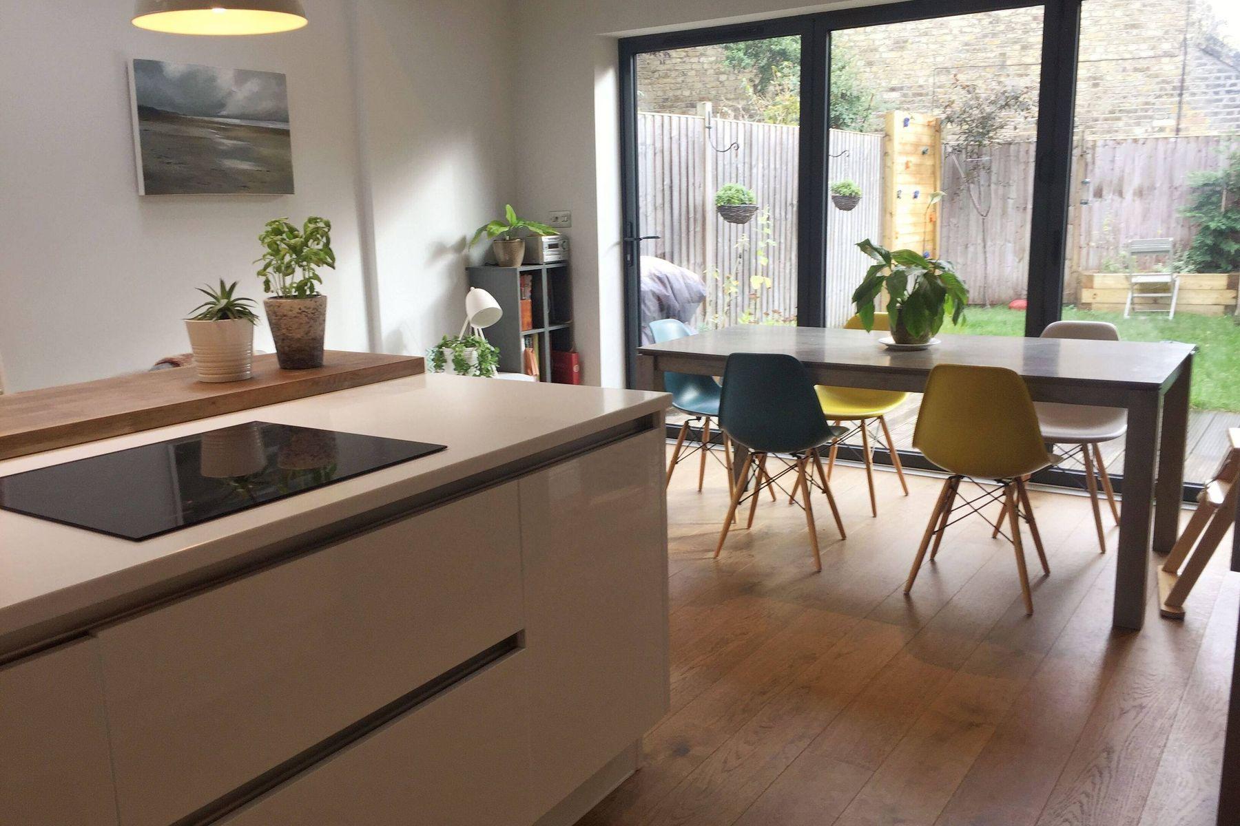Innenraum einer Küche mit Arbeitsplatte, Stühlen und Tisch