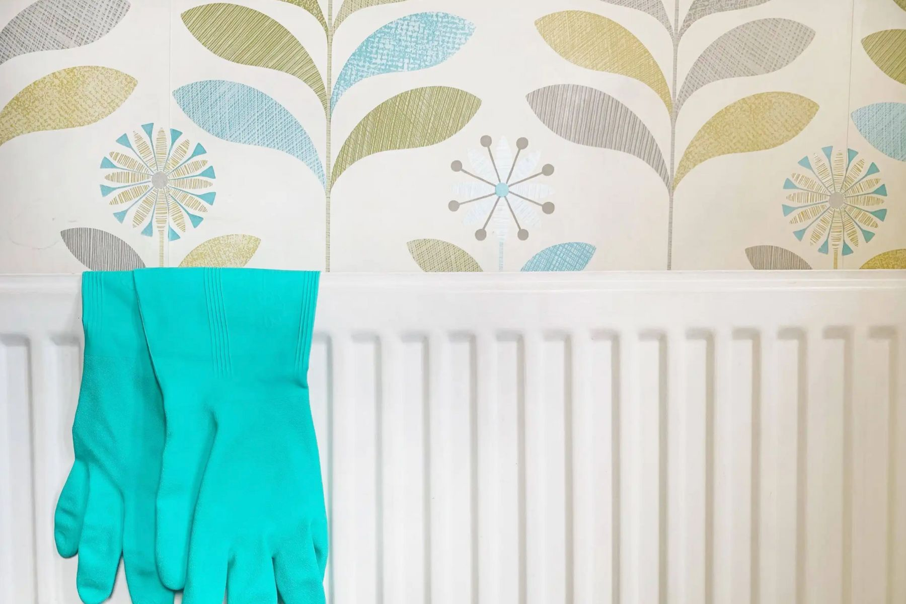 White radiator with a pair of green gloves