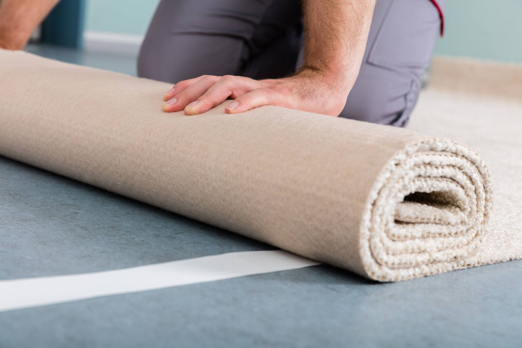 male hand rolling carpet on the floor