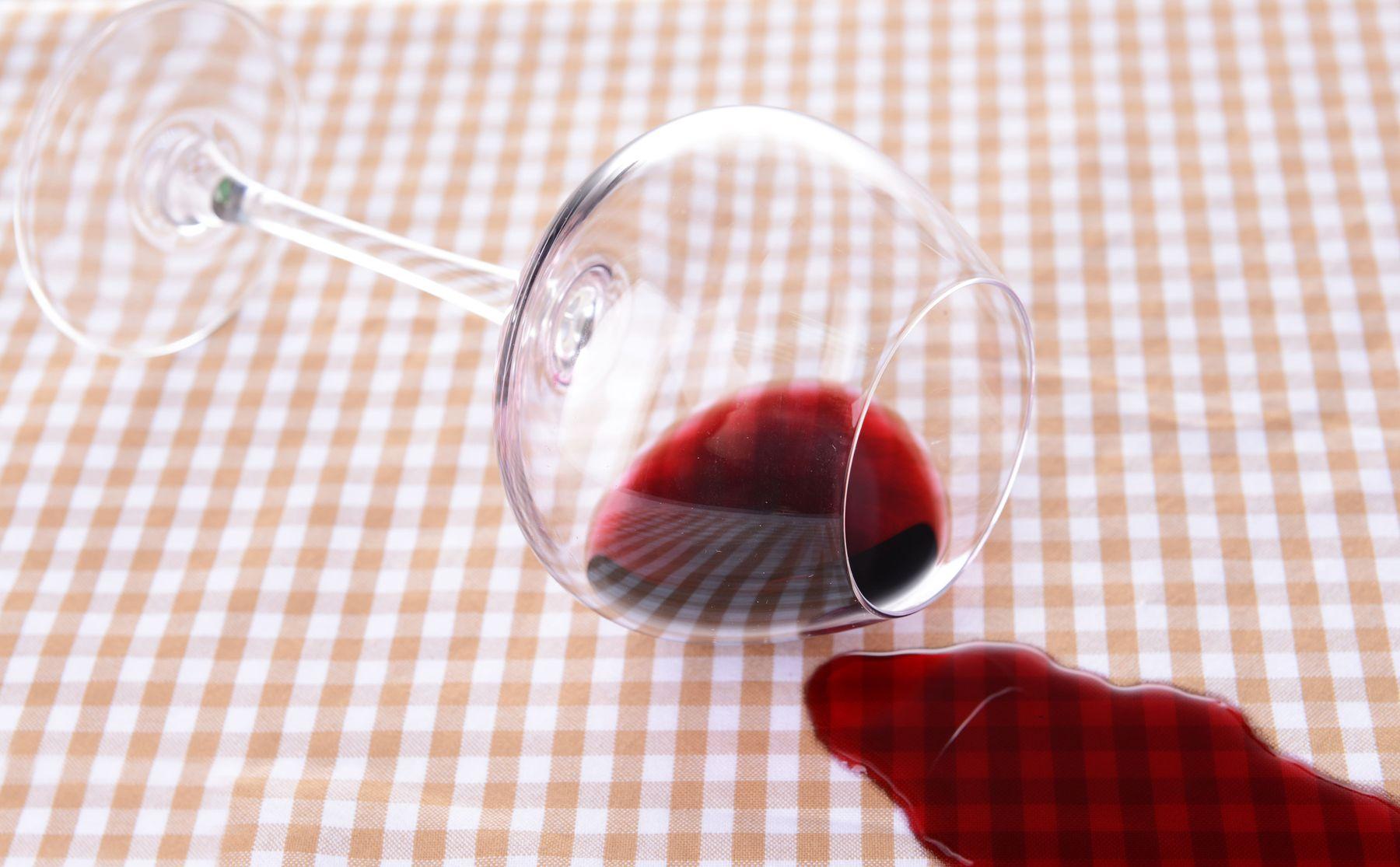 Taça de vinho derrubada sobre toalha de mesa quadriculada