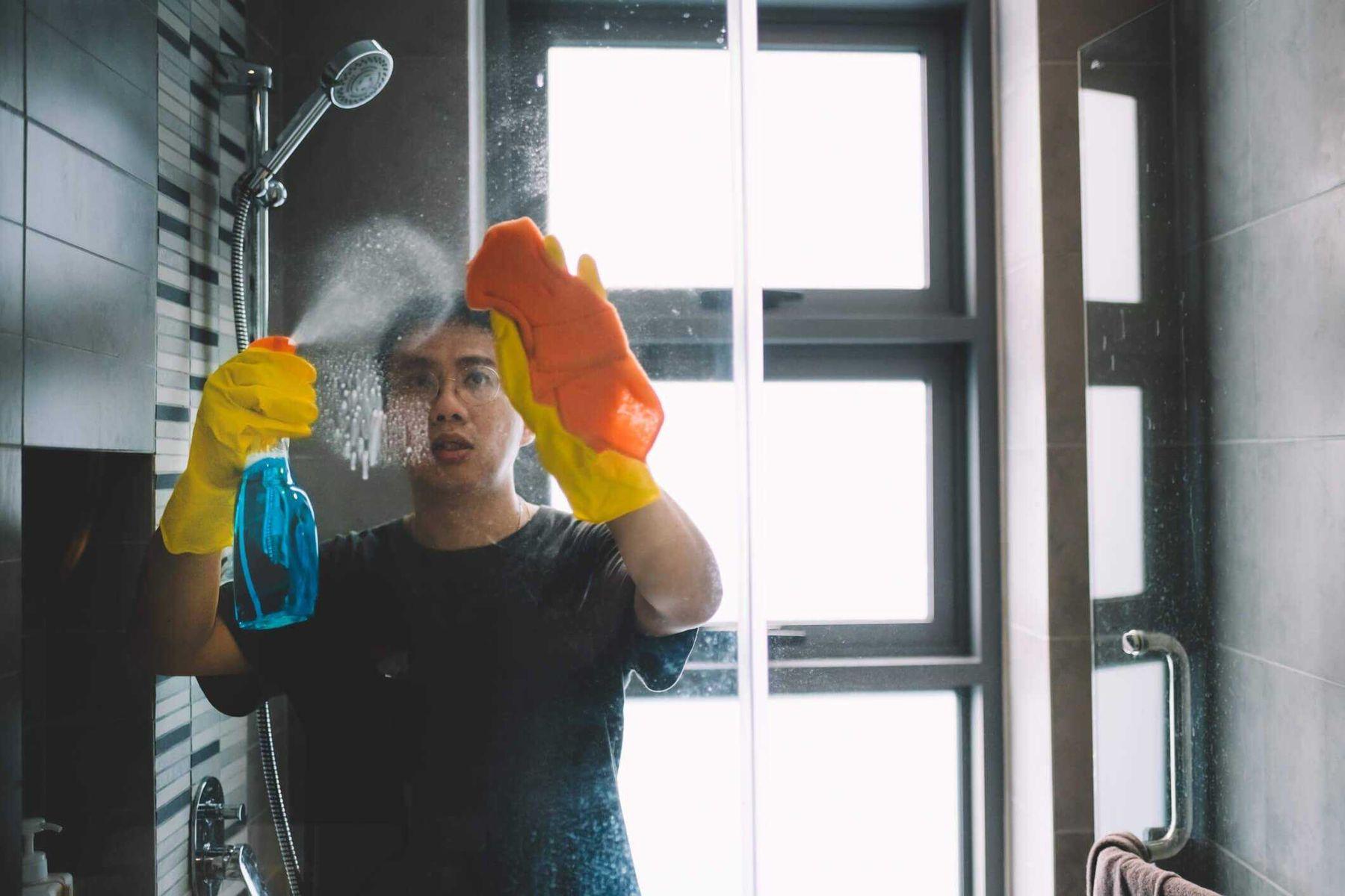 homem-de-luvas-limpando-box-banheiro
